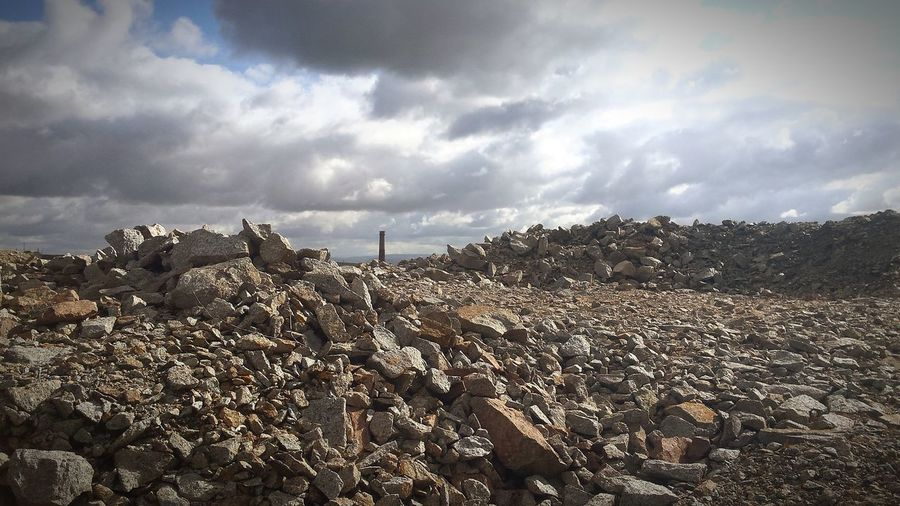 Stack of stones on land against sky