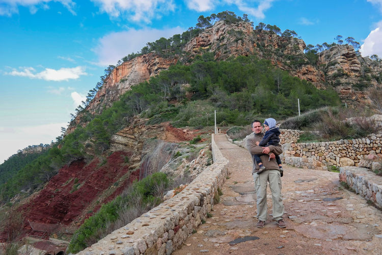 Full Length Of Man Carrying Son While Standing On Pathway Against Mountain