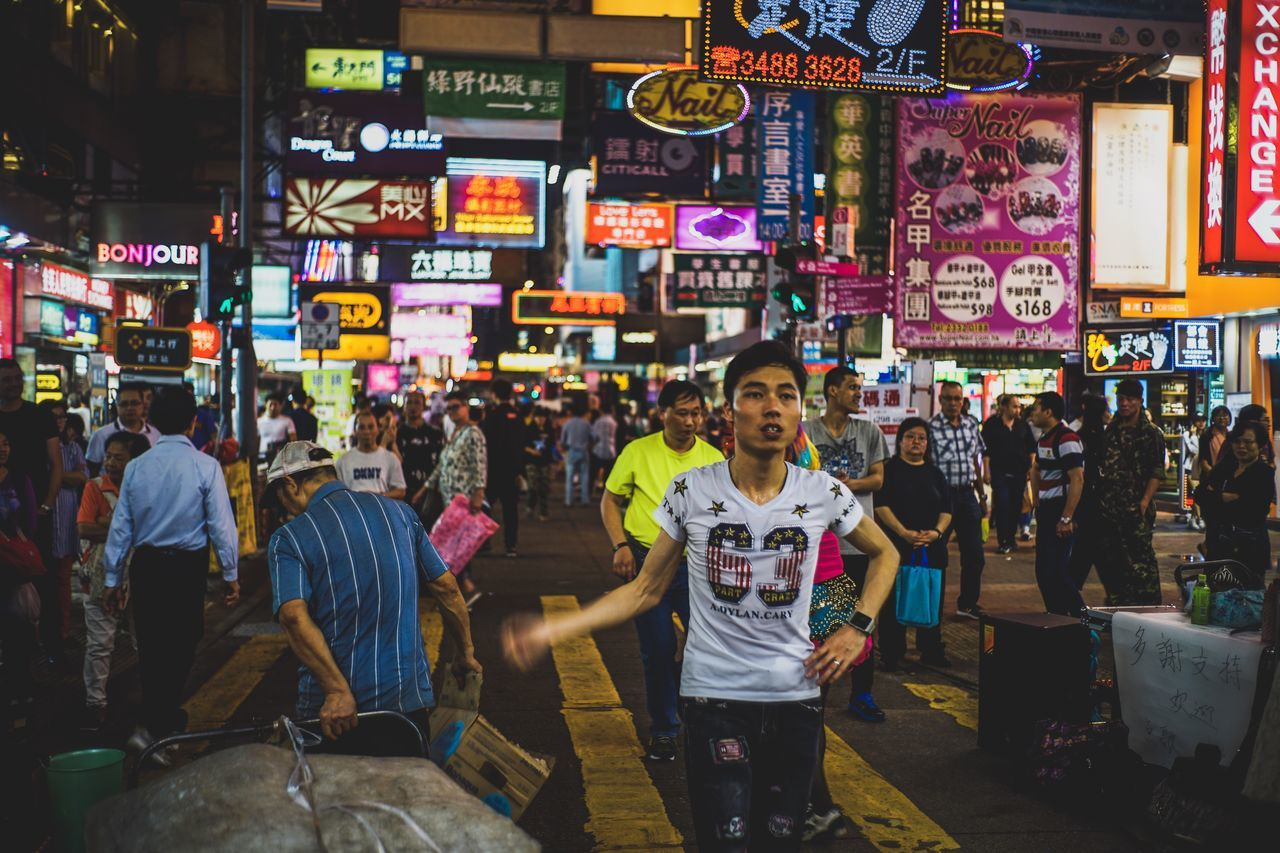 real people, text, retail, men, night, women, market, large group of people, outdoors, communication, store, illuminated, neon, standing, architecture, lifestyles, building exterior, food, city, people
