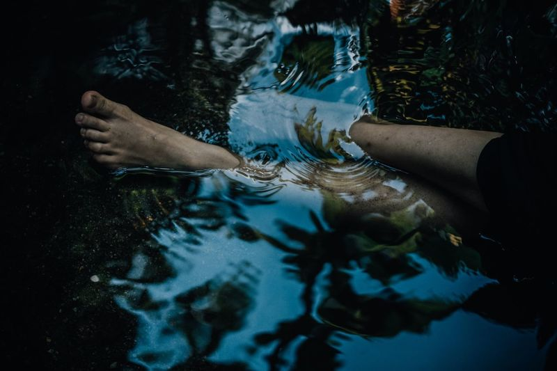 Cropped Image Of Persons Legs In Pond