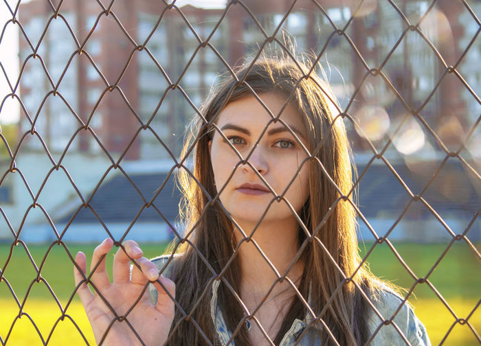 Portrait of young woman looking through fence outdoors
