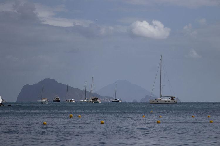 Sailboats sailing in sea against sky