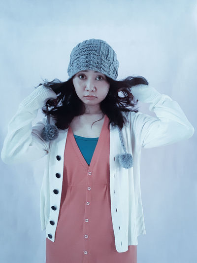 Portrait of young woman standing wearing winter clothes playing with the hair cheerfully