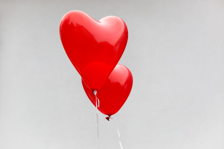 Low Angle View Of Red Heart Shape Balloons Against Wall