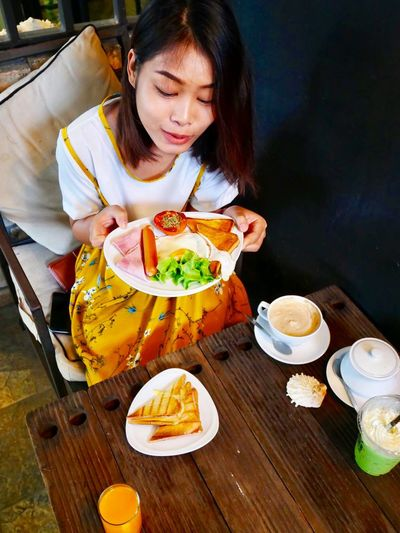 High angle view of young woman holding food in plate while sitting at table