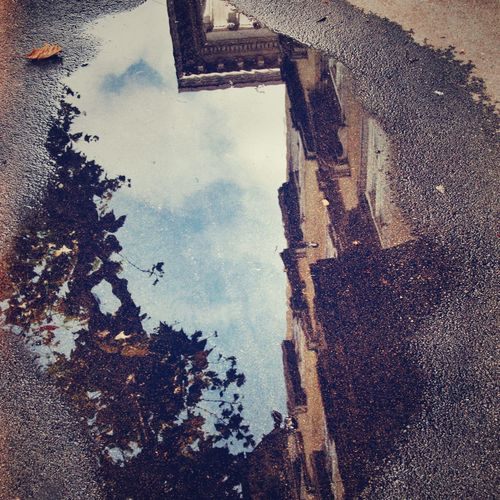 Building and sky reflecting in puddle on street
