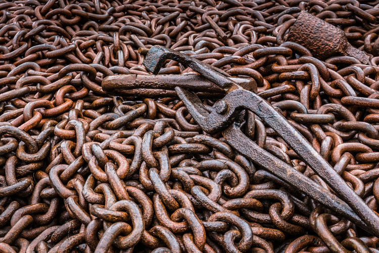 A pile of rusting large gauge chain at The Black Country Living Museum, Dudley in the West Midlands. Black Country Museum Industrial Rusted Chain Rusted Chain Link... Black Country Living Museum Blacksmith Tongs Chain Chain Making Chainmaker Chains Close-up Heavy Chains Heavy Metal Interlinked No People Rusted Rusted Metal Texture Rusting Rusty Tongs