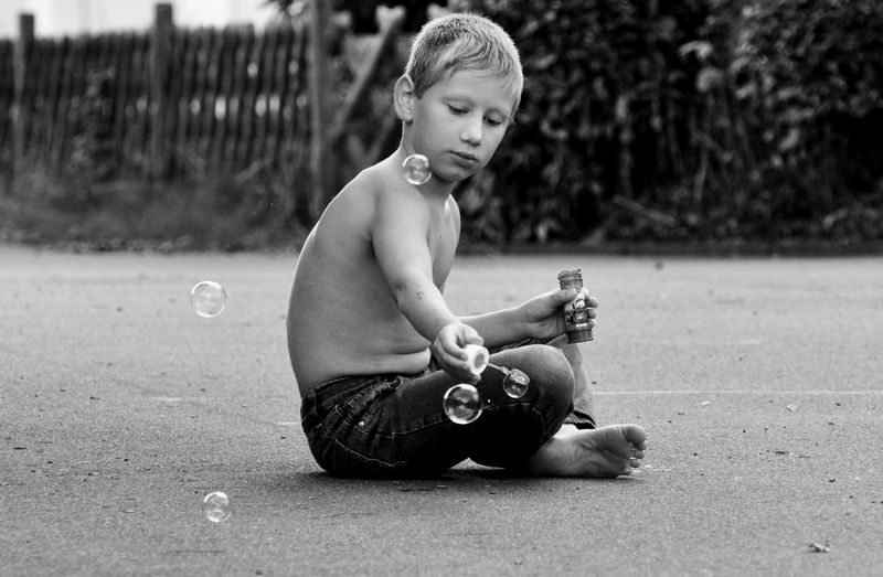 Shirtless boy playing with bubbles on road