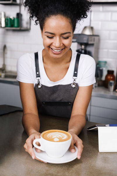 Apron Business Latte Waitress Young Black Hair Cafeteria Cheerful Coffee - Drink Coffee Cup Curly Hair Drink Food And Drink Freshness Holding Indoors  One Person Owner Real People Smiling Women Young Adult