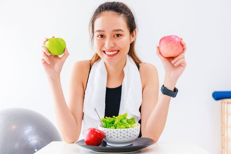Portrait of woman holding apple against white background