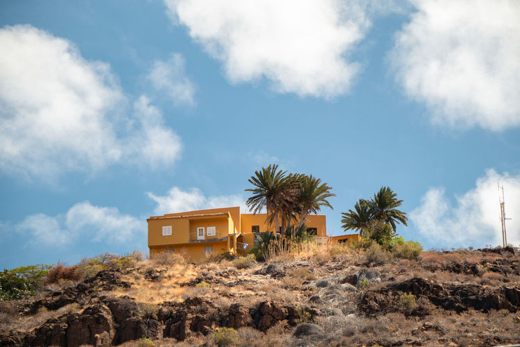 Palm trees and house against sky
