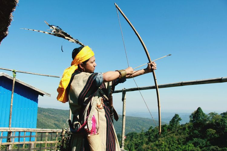 Man holding bow and arrow while standing against sky
