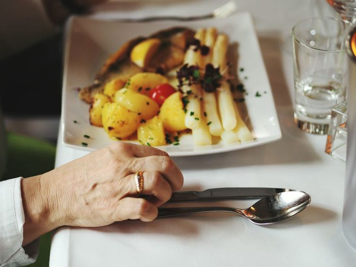 Cropped Hand By Food On Table