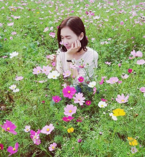 Woman with pink flowers on field