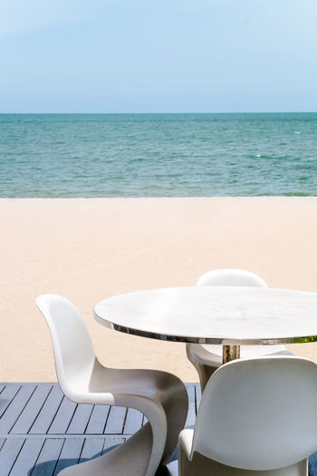 Empty chairs and table by sea against sky