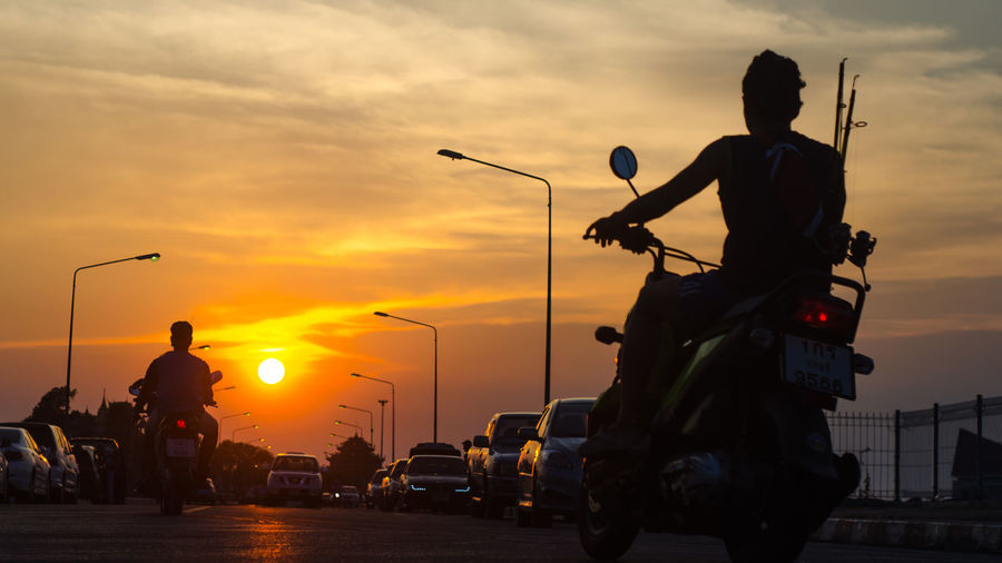Rear view of men driving motorcycles against sky during sunset
