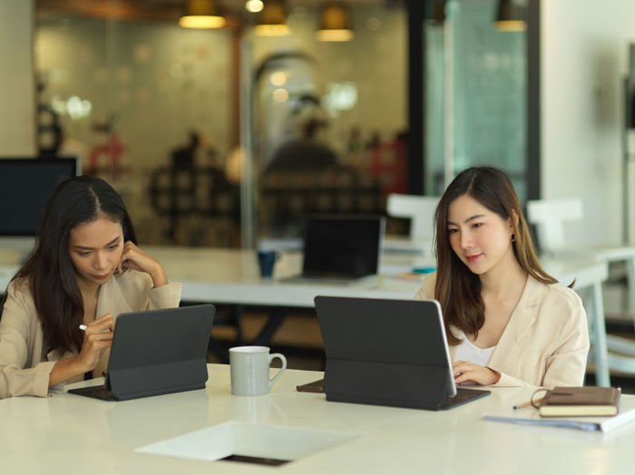 Beautiful businesswomen using computer while sitting in office