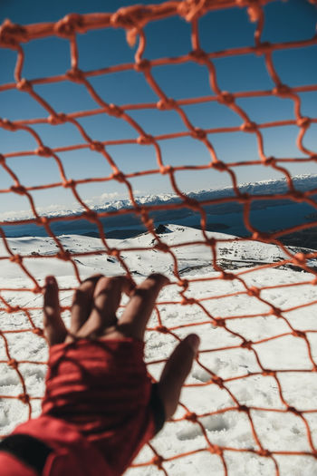 Cropped hand of woman holding net against sky during winter