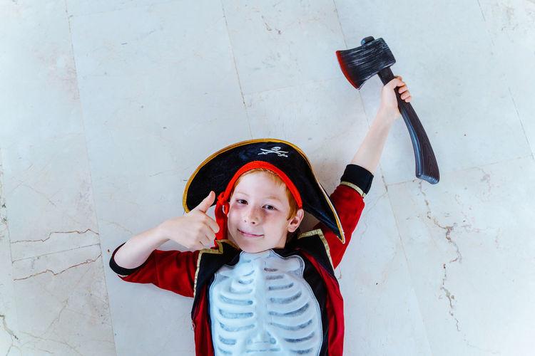 Portrait of cute boy holding camera against wall