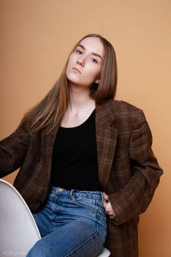 Portrait of a young woman sitting against wall