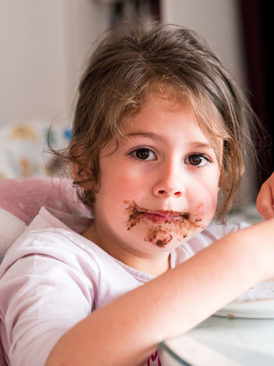 Caucasian girl with chocolate messy face indoors Indoors  Child Portrait Childhood Headshot Front View Innocence Messy Chocolate Eating Small Little Caucasian Girl Kid Face Dirty Dessert Expression Beautiful Happy Cheerful Adorable Toddler  Cake Pretty Joy