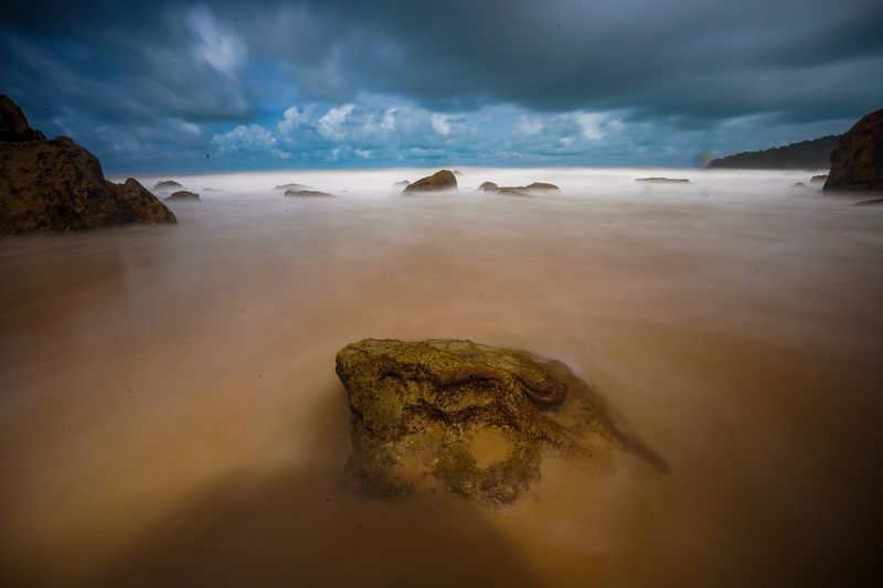 A scenic view of a long exposure shot at a stony beach in Kuching, Sarawak Water Sea Sky Cloud - Sky Land Beach Sand Scenics - Nature Beauty In Nature Environment Nature Rock - Object Solid Tranquility Rock Coastline Outdoors Landscape Travel Destinations Horizon Over Water