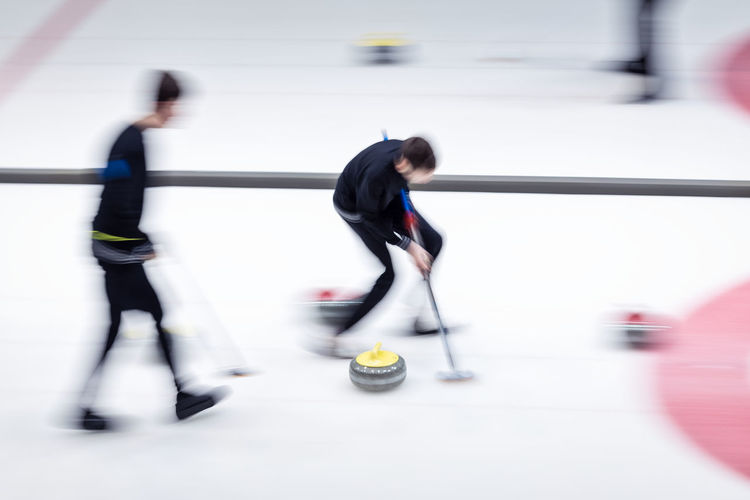 Blurred motion of people playing curling