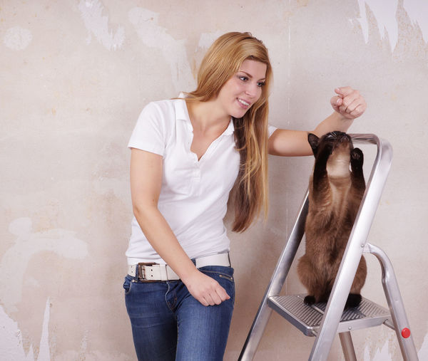 Smiling beautiful woman playing with siamese cat on ladder against wall