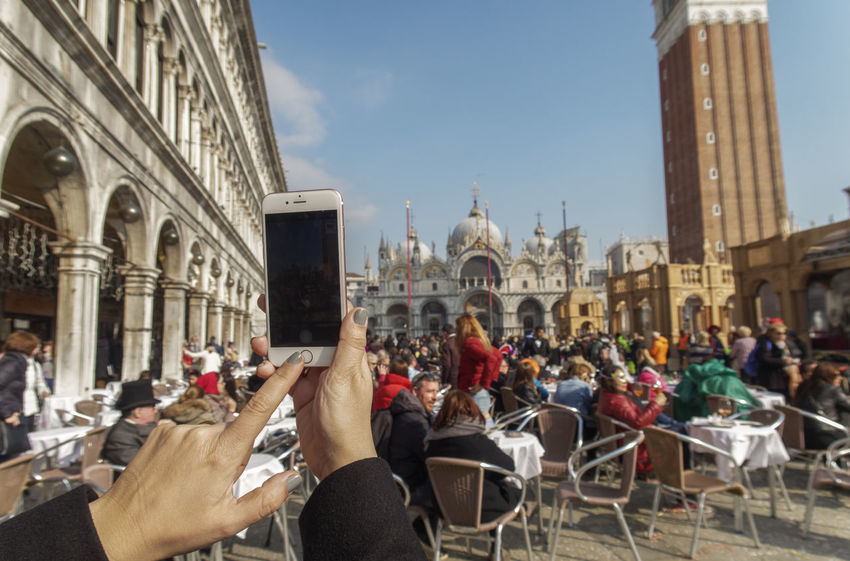 Hand holding mobile phone in Venice, Italy with blurred image of square. A female hand holding a phone at Piazza San Marco full of people on a sunny day. Background Blurred Communication Connection Device Female Gadgets Hold Holding Mobile Phone Internet Italy Mobile Mobile Phone Piazza San Marco Venice,Italy Smartphone Social Telephone Touch Touchpad Tourist Travel Destinations Venice Venice Square Venice, Italy Wireless Technology Mobile Conversations Mobile Conversations