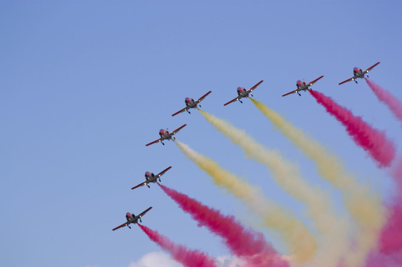 airshow, teamwork, smoke - physical structure, speed, vapor trail, airplane, low angle view, fighter plane, military airplane, flying, air vehicle, performance, transportation, motion, aerobatics, air force, formation flying, blue, mode of transport, risk, multi colored, skill, stunt, clear sky, mid-air, arts culture and entertainment, sky, cooperation, arrangement, day, acrobatic activity, outdoors, no people, coordination