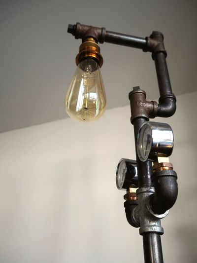 Close-up of light bulb against wall