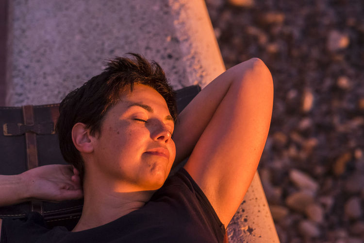 Woman sleeping on retaining wall in sunny day