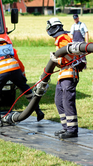 Firefighters holding pipe on road amidst grass field