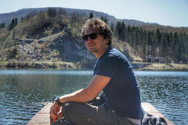 Young man sitting by sunglasses on lake