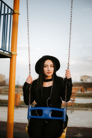 Portrait of beautiful young woman sitting on swing at playground against sky