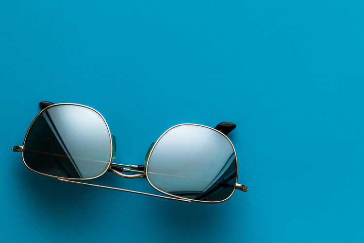 Low angle view of sunglasses against blue sky