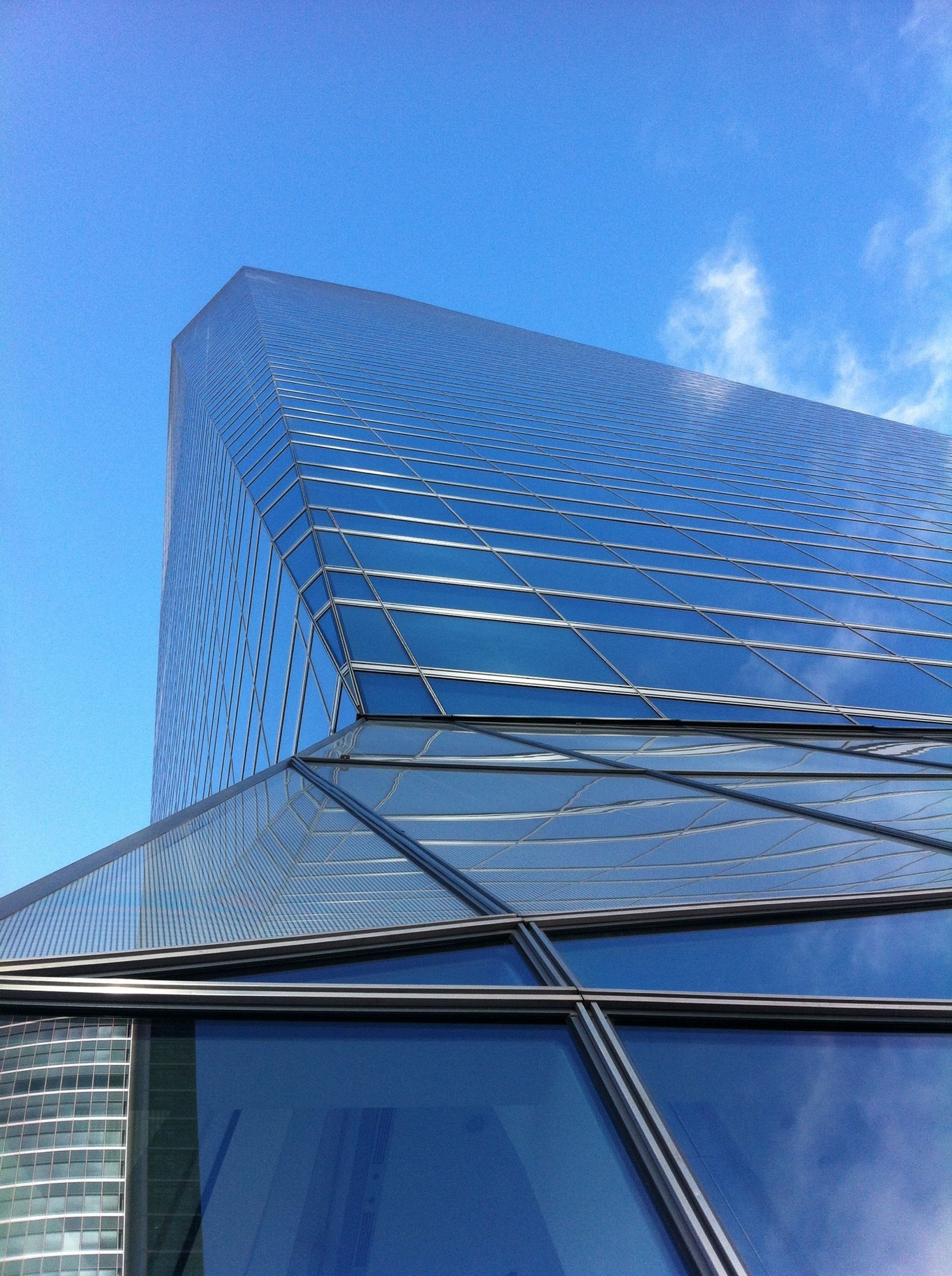 low angle view, architecture, built structure, building exterior, modern, blue, office building, sky, skyscraper, tall - high, building, city, tower, pattern, glass - material, day, clear sky, reflection, outdoors, no people