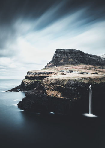 Where the land touches the ocean. Location: Gásadalur, Faroe Islands. Equipment: Fujifilm X-T2 + XF14mm. EyeEm Best Shots Gasadalur Beauty In Nature Cloud - Sky Day Faroe Islands Idyllic Land Mountain Mountain Peak Nature No People Non-urban Scene Outdoors Rock Rock - Object Rock Formation Scenics - Nature Sea Sky Solid Tranquil Scene Tranquility Water Waterfall