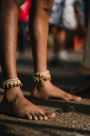 Low section of man wearing anklet standing on road