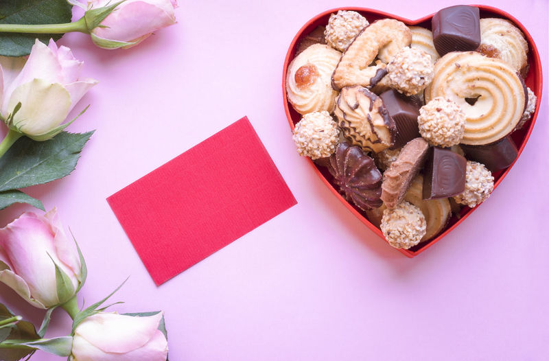 Close-up of flowers with chocolate in heart shape against pink background