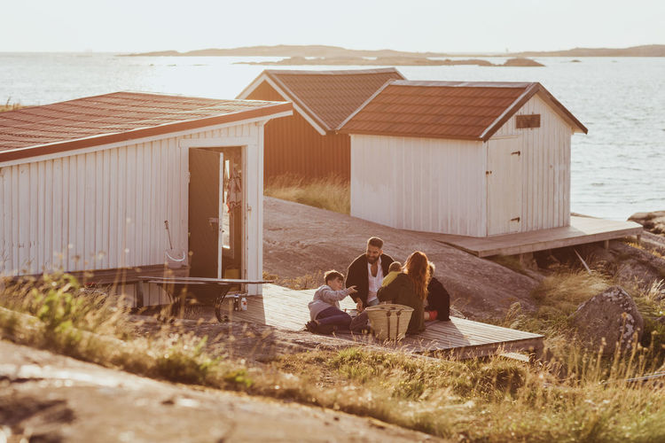 People sitting on beach by house