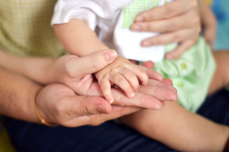 Midsection Of Couple And Baby Holding Hands