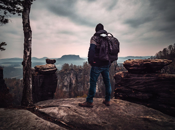 A photo taken in the Saxon Switzerland Rear View Sky Cloud - Sky Real People Standing Full Length Men People Nature Lifestyles Beauty In Nature Leisure Activity Rock Scenics - Nature Casual Clothing Rock - Object Activity Mountain Tranquility Outdoors Looking At View Taking Photos Wanderlust Solitude Exploring