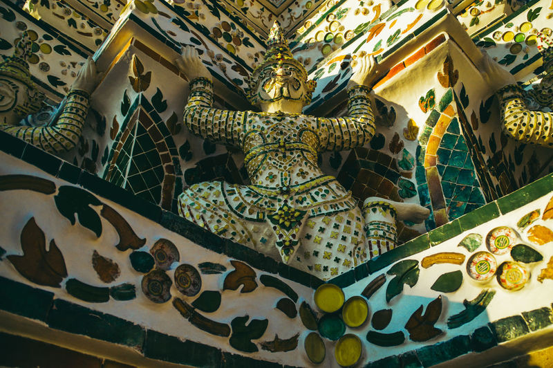 Low angle view of thai statue in wat arun temple