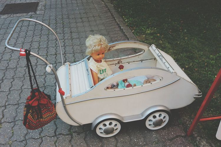 High angle view of doll in toy car on footpath