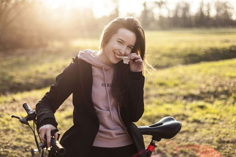 Portrait of smiling young woman with bicycle standing in park