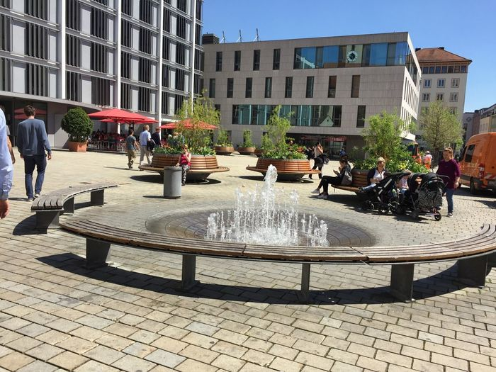Architecture Building Exterior Built Structure City Day Drinking Fountain Fountain Large Group Of People Lifestyles Men Motion Outdoors People Real People Spraying Sunlight Tree Water