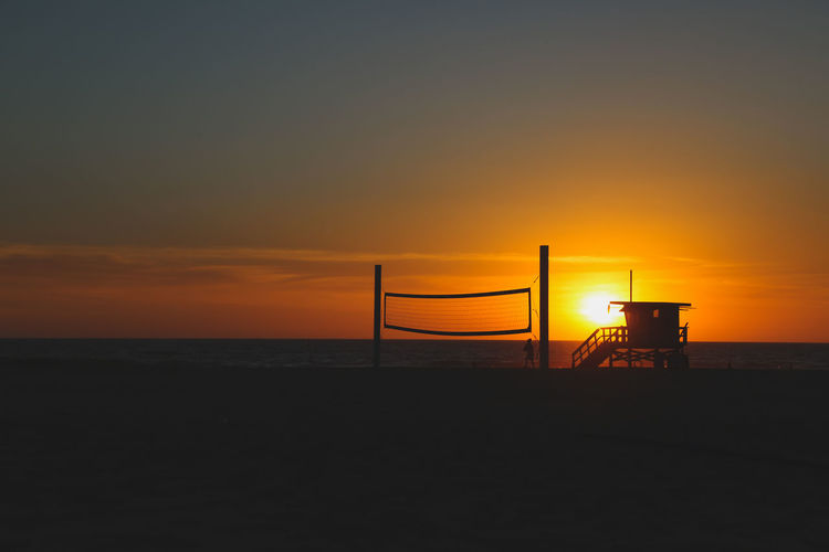 lifeguard hut and volleyball net on hermosa beach in Los Angeles at sunset Los Angeles, California Hermosa Beach Beach Pacific Ocean Scenics Travel Destinations Vacations Leisure Pacific Coast Beach Life Volleyball Net Tranquility Peaceful Beach Volleyball Water Sea Sunset Beach Silhouette Net - Sports Equipment Orange Color Lifeguard  Romantic Sky Volleyball - Sport Moody Sky Atmospheric Mood Lifeguard Hut Seascape Shore Sun