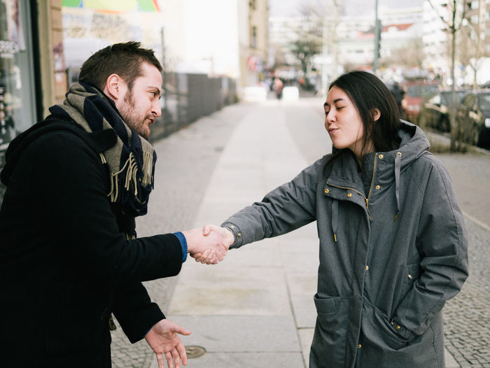 Friends shaking hands on sidewalk in city
