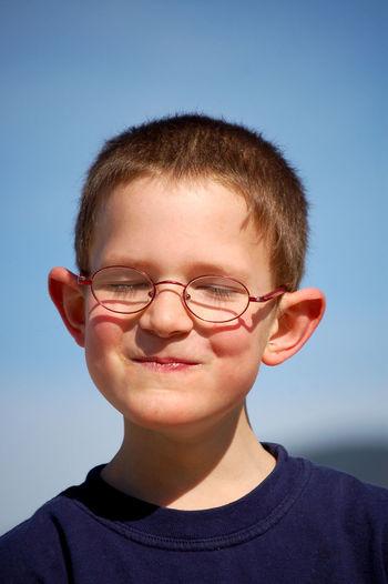 Close-up portrait of smiling boy against sky